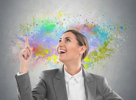 Colorful Thinking. Business woman against gray background and colorful splashes photo