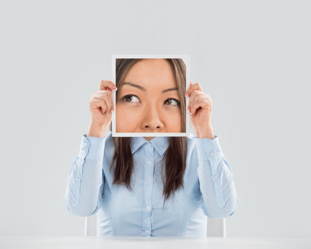 Young woman holding a picture of eyes in front of her face Imagens
