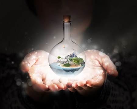 Female hands holding corked glass bottle with beautiful island and sea inside. Confidence, stability, insurance concept