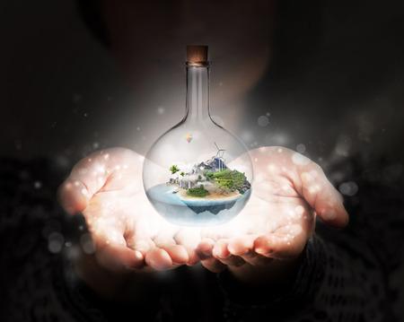 Mujeres manos sosteniendo la botella de vidrio con corcho con hermosa isla y el mar interior. La confianza, la estabilidad, el concepto de seguro