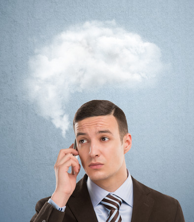 Businessman and a cloud of thoughts on a blue background photo