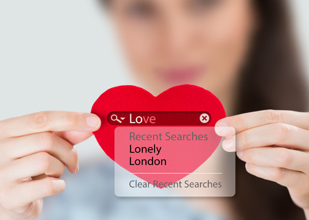 searches: Love search. Young woman holding red heart with love search options Stock Photo