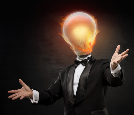 Businessman with burning lamp head on black background. Welcoming gesture photo