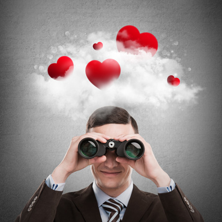 holidays for couples: Red hearts flying in cloud overhead of man looking through binoculars. Valentines day background
