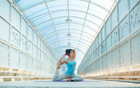 outdoor training: Woman doing stretching yoga exercises outdoors on the bridge. Full Length