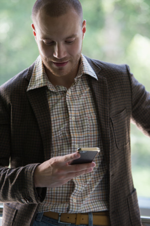 Happy young businessman reading text message on smartphone photo