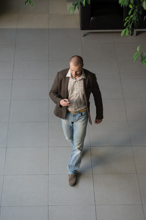 Attractive businessman using his cell phone in office building lobby. Top view