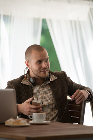 Business man resting at cafe and listening music using vintage headphones photo