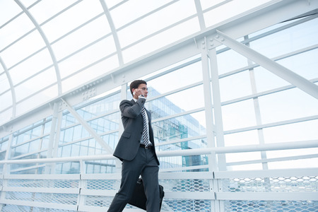 business traveler: Man on smart phone - young business man in airport. Businessman using smartphone inside office building or airport.