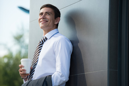 Businessman drinking coffee outdoors. Business man smiling happy holding disposable coffee cup standing near modern building. photo