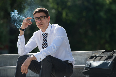 Goed geklede zakenman roken zittend op een straat stoep Stockfoto