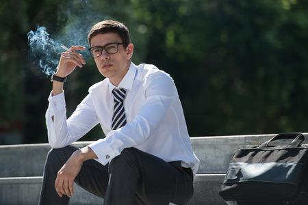 cigarette: Well dressed business man smoking sitting on a street sidewalk Stock Photo