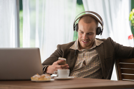 vintage radio: Business man resting at cafe and listening music using vintage headphones Stock Photo