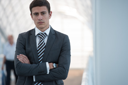 Portrait of handsome confident young businessman standing arms crossed, looking at camera. photo