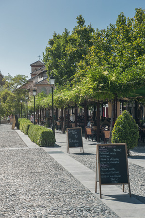 paseo: Outdoor cafe at the famous touristic boulevard Paseo de los Tristes, near Alhambra monument, Granada, Spain