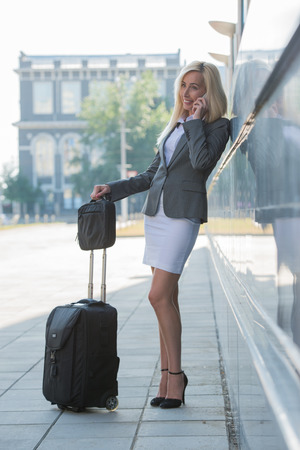 Businesswoman holding a suitcase on a city street photo