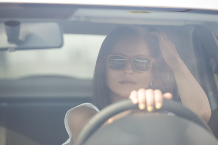 Girl wearing sunglasses driving white car photo