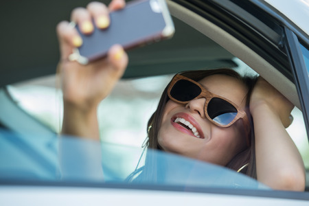 take a smile: Holidays and tourism concept - smiling teenage girl taking selfie picture with smartphone camera outdoors in car Stock Photo