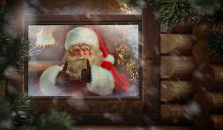 toy shop: Santa Claus thumbs up through his workshop window in the north pole to see outside. Christmas Eve