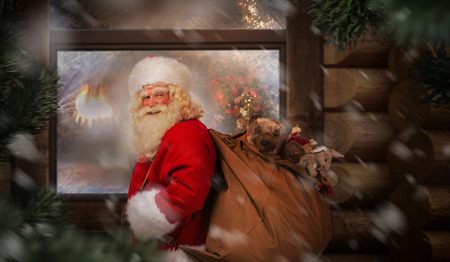 carefully: Santa Claus carrying his sack near wooden house at night outdoor. Christmas eve Stock Photo