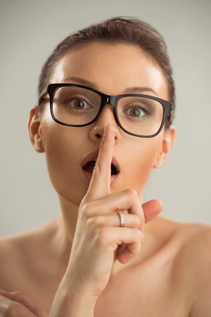 Closeup photo of woman wearing glasses and making a hush gesture photo