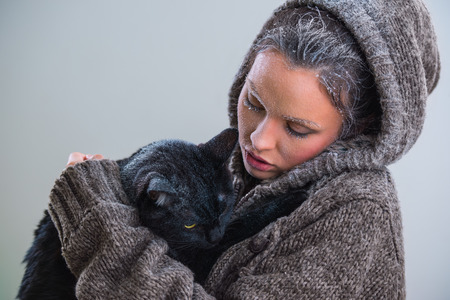 vagabond: Winter portrait of young kind woman holding big black cat. Frost and snow on them
