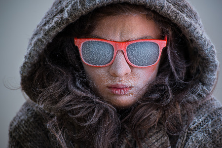 showoff: Frozen woman wearing jacket and sunglasses with snow on her face. Fashion portrait