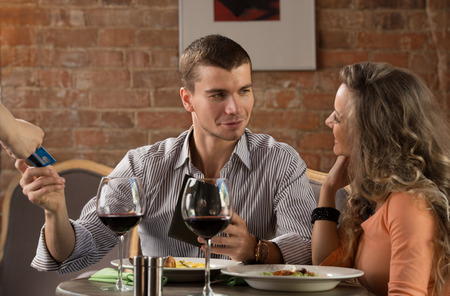 Happy couple in restaurant pay cash free by credit card electronic security money photo