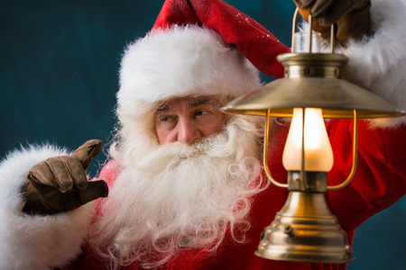 believable: Santa Claus is holding a shining lantern outdoors at North Pole at night