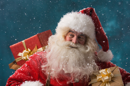 distributing: Photo of happy Santa Claus outdoors in snowfall carrying gifts to children