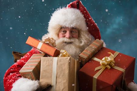 Foto van de gelukkige Kerstman buiten in de sneeuw het dragen van geschenken aan kinderen