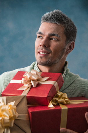 carries: Happy young man carries a lot of presents outdoors in winter. Frost on his face