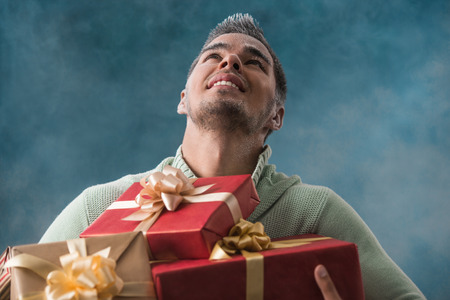 cool backgrounds: Happy young man carries a lot of presents outdoors in winter. Frost on his face