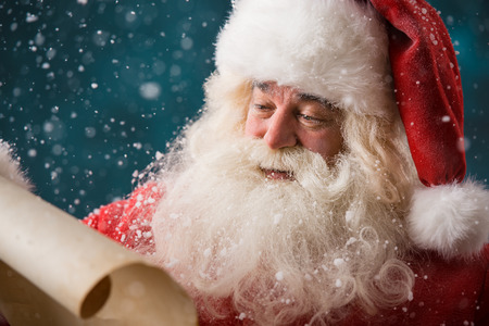 Portrait of happy Santa Claus reading Christmas letter outdoors at north pole at snowfall Stock Photo