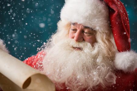 papa noel: Retrato de feliz de leer la carta de Navidad de Santa Claus al aire libre en el polo norte en las nevadas