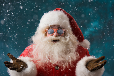 Santa Claus wearing sunglasses dancing outdoors at North Pole in snowfall. He is celebrating Christmas after hard work