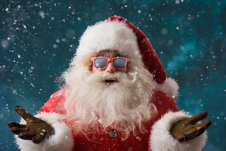 winter party: Babbo Natale indossando occhiali da sole che ballano all'aperto al Polo Nord in precipitazioni nevose. Si festeggia il Natale dopo il duro lavoro