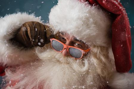 De Kerstman draagt een zonnebril buitenshuis dansen op Noordpool in sneeuwval. Hij viert kerst na hard werken Stockfoto