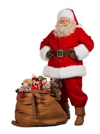 papa noel: Retrato de cuerpo entero de un Santa Claus que presenta cerca de una bolsa llena de regalos aislados sobre fondo blanco