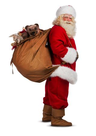 �santaclaus: Real Santa Claus llevando gran bolsa llena de regalos, aislado en fondo blanco Foto de archivo