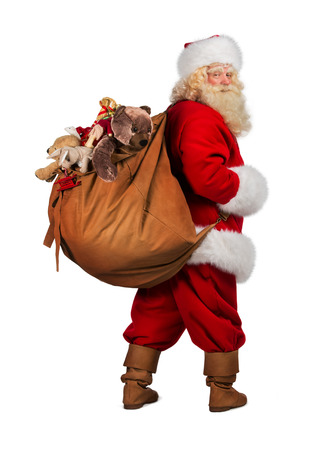 Full length portrait of Real Santa Claus carrying big bag full of gifts from behind, isolated on white background
