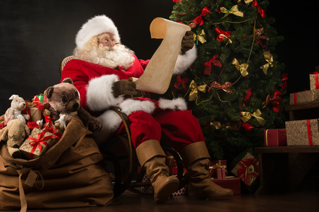 sacks: Portrait of happy Santa Claus sitting at his room at home near Christmas tree and big sack and reading Christmas letter or wish list
