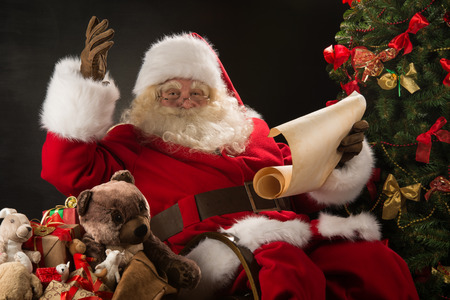 Portrait of happy Santa Claus sitting at his room at home near Christmas tree and big sack and reading Christmas letter or wish list photo