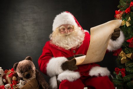 santa claus�: Retrato de feliz Santa Claus sentado en su habitaci�n en la casa cerca del �rbol de Navidad y el saco grande y la lectura de la carta de Navidad o en la lista de deseos