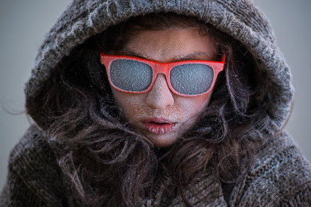 Frozen woman wearing jacket and sunglasses with snow on her face. Fashion portrait