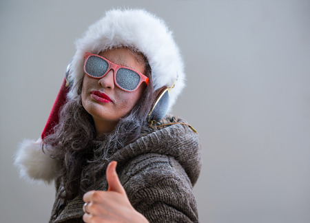 Woman wearing Santa Claus hat and sunglasses listening to music with her headphones and thumbs up. Winter season series fashion portrait photo