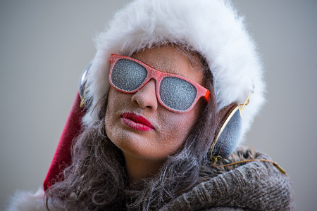 Woman wearing Santa Claus hat and sunglasses listening to music with her headphones. Winter season series fashion portrait photo