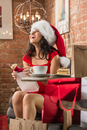 Charming woman wearing Santa Claus hat opening Christmas gift in a restaurant photo