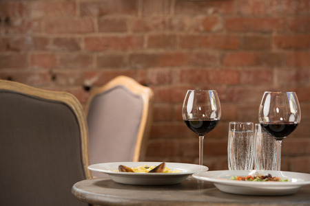 degustating: Vintage restaurant interior. Closeup of table with two meals and wine glasses. Prepared for two
