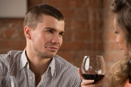 Young happy couple on romantic date drinking glass of red wine at restaurant, celebrating valentine day photo